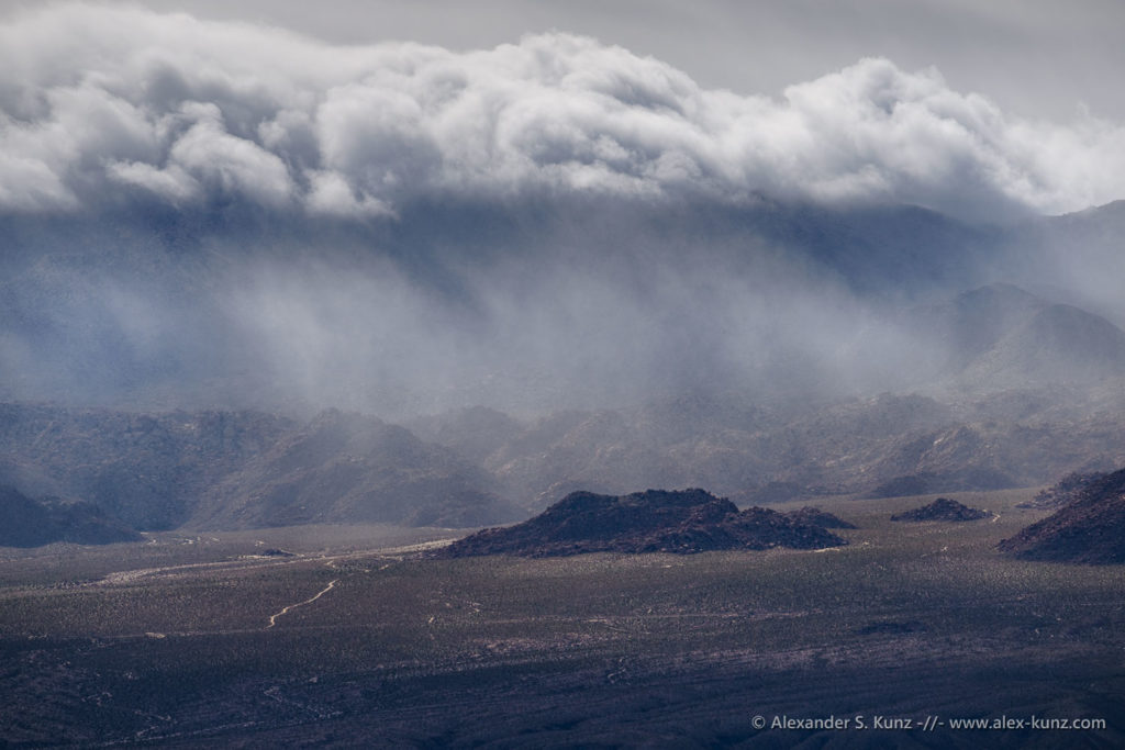 Clouds accumulate over the eastern edge of the Tierra Blanca Mountains and unload precious rain over the desert. Seen from Carrizo Mountain, January 2019.